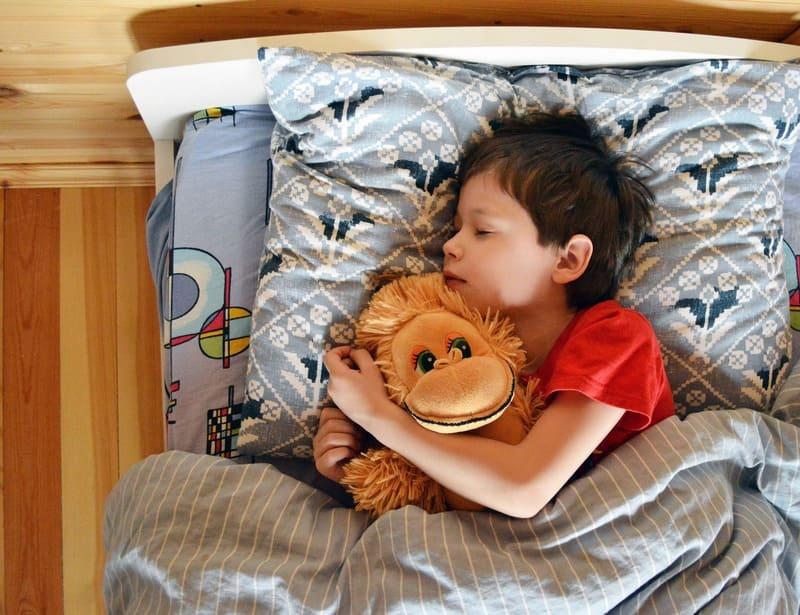 niño durmiendo en su cama abrazado a un osito