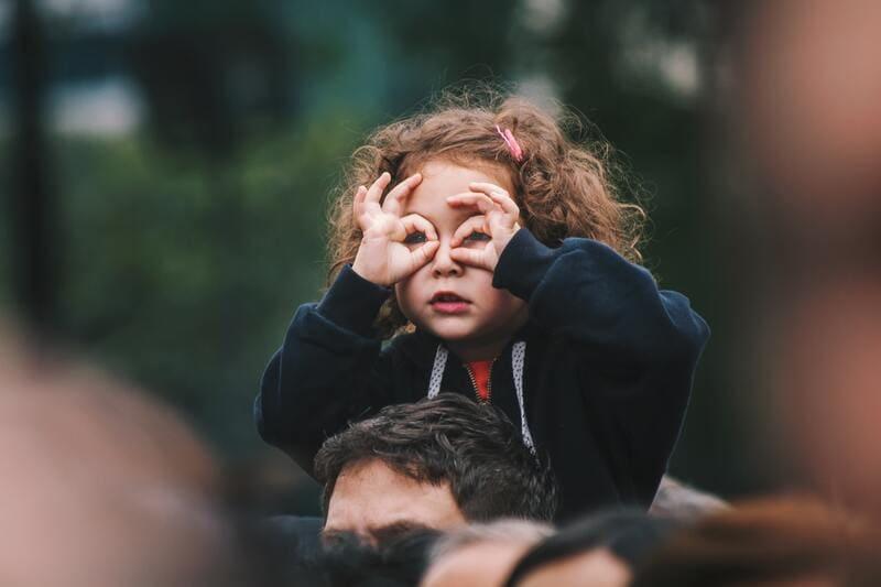 niña con manos en los ojos buscando