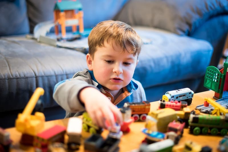 niño jugando con juguetes y trenes