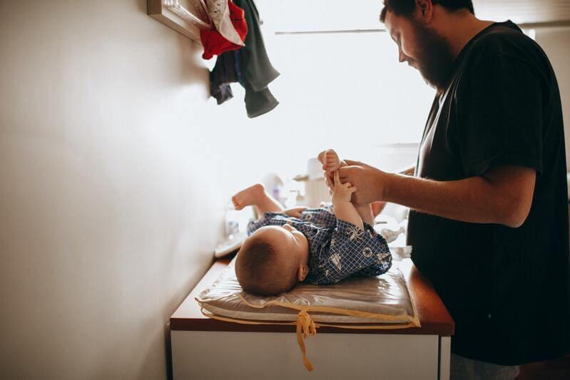 hombre cambiando el pañal a bebe